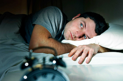 sleep symptoms man lying in bed can't sleep